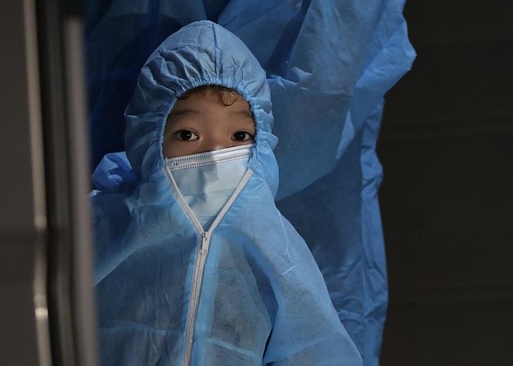 Một em bé tại phường Thanh Xuân Trung, quận Thanh Xuân đi cách ly tối 1/9. Ảnh: Giang Huy
