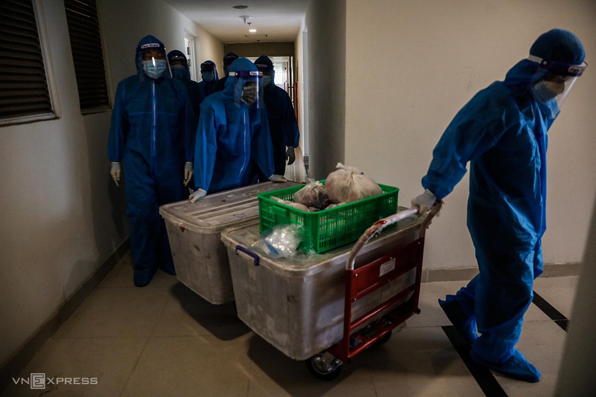 Nhân viên y tế và dân quân tự vệ vận chuyển cơm cho các F0 tại Bệnh viện dã chiến số 3. Ảnh: Hữu Khoa.