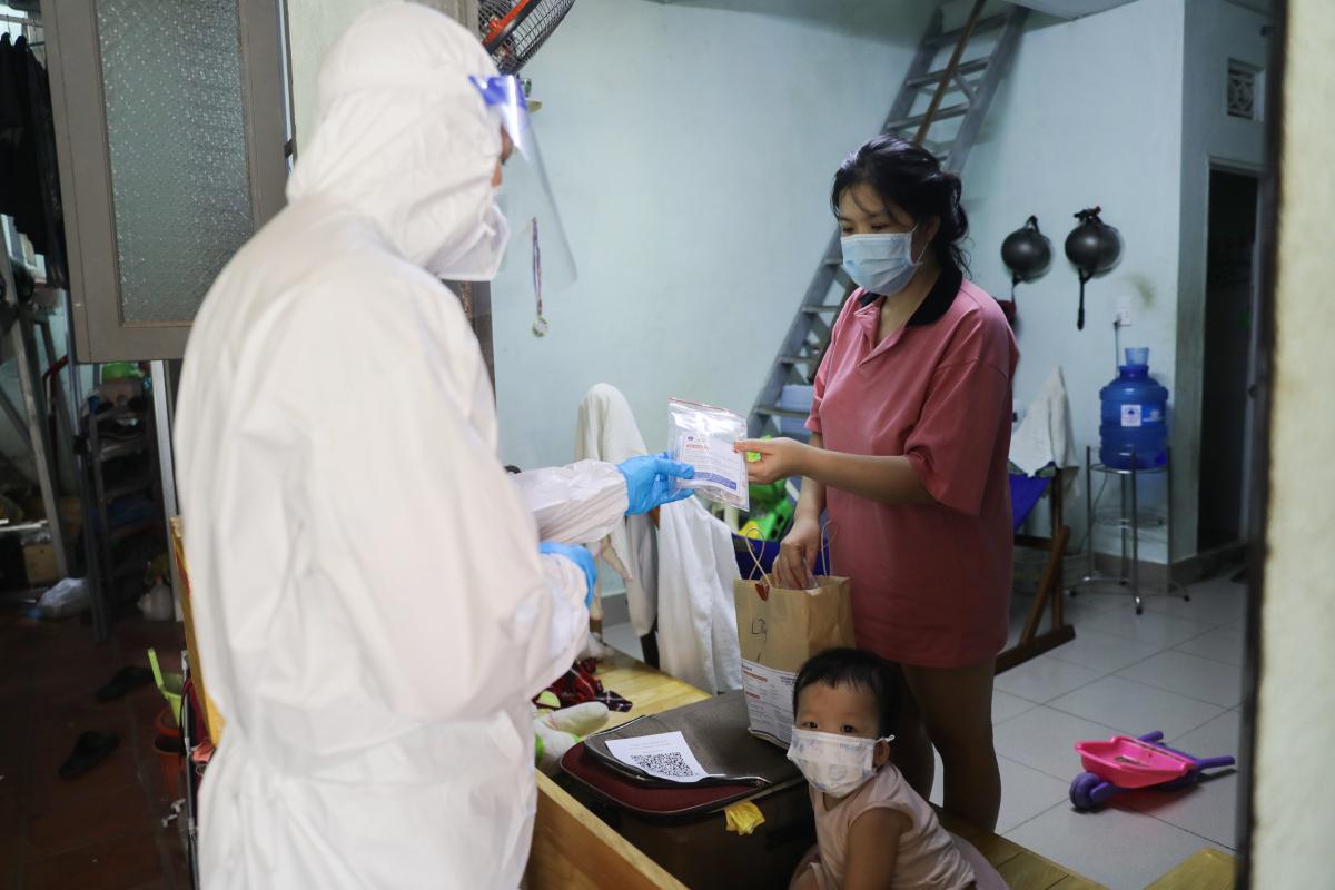 Nhân viên y tế phường Linh Tây, TP Thủ Đức, thăm khám và phát thuốc cho chị Mỹ Duyên, 28 tuổi, một F0 đang điều trị tại nhà, ngày 3/9. Ảnh: Quỳnh Trần