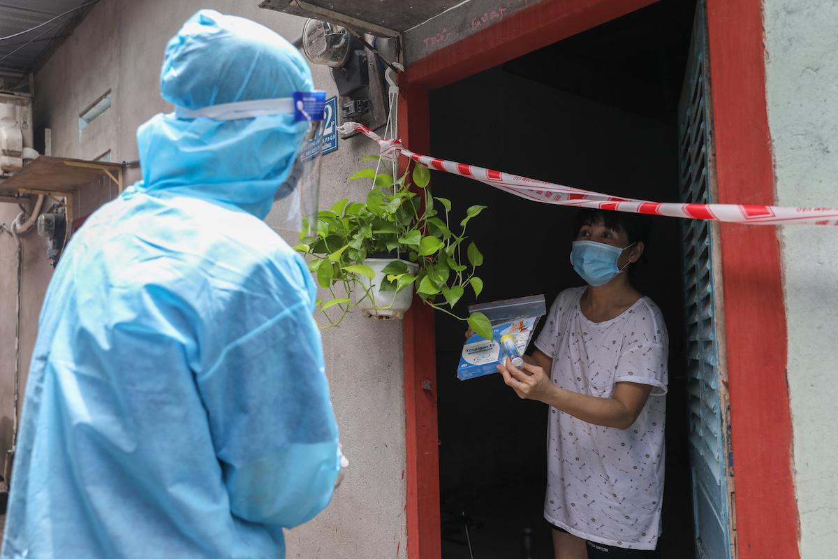 Nhân viên y tế phường 3, quận 8 đến thăm khám, tặng thuốc cho người mắc Covid-19 đang điều trị tại nhà, ngày 29/8/2021. Ảnh: Quỳnh Trần/VnExpress