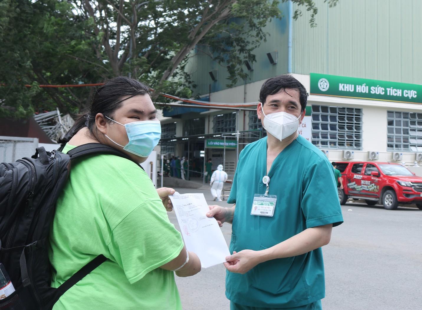 Tiến sĩ Đỗ Ngọc Sơn trao giấy ra viện cho một bệnh nhân 24 tuổi, nặng 130 kg, mác Covid-19 rất nặng, được cứu sống tại Trung tâm. Ảnh: Thành Dương