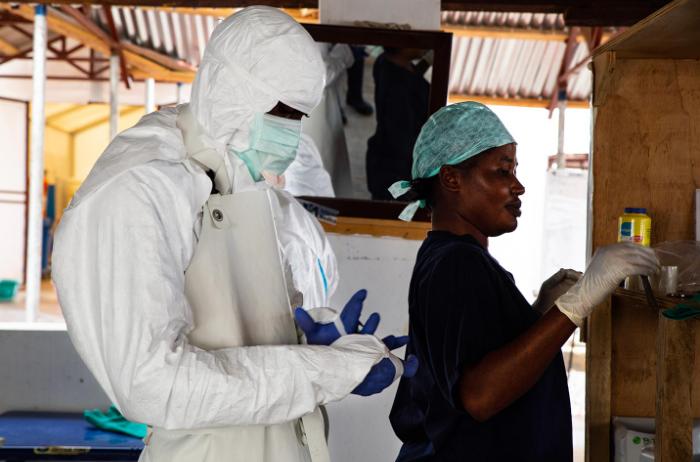nhân viên y tế chuẩn bị bước vào khu vực nguy hiểm của một trung tâm điều trị ebola để kiểm tra sự tiến triển của bệnh nhân.