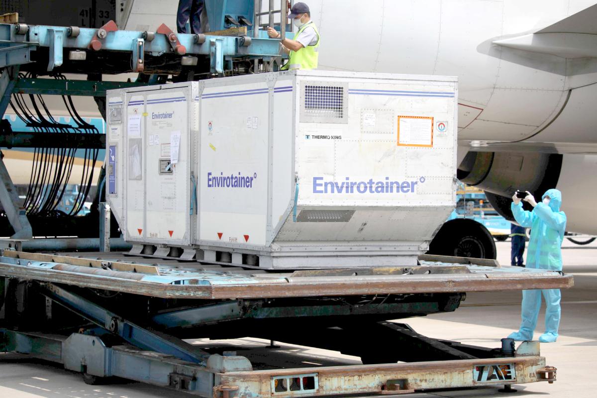 Một thùng lạnh chứa vaccine AstraZeneca đang được đưa từ máy bay xuống mặt đất tại sân bay Tân Sơn Nhất. Ảnh: Phong Lan.