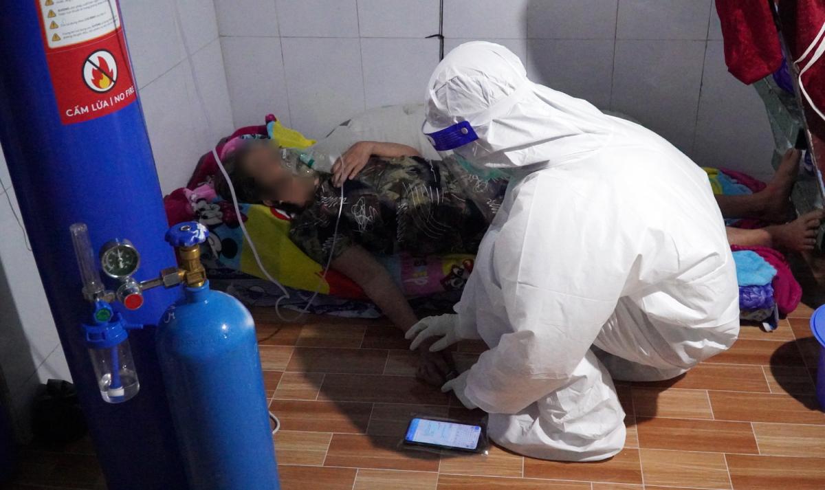 Một bệnh nhân Covid-19 điều trị tại nhà có dấu hiệu suy hô hấp được nhân viên y tế hỗ trợ thở oxy. Ảnh: Thu Huế