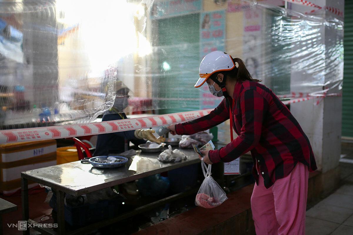 Người dân mua hàng tại chợ truyền thống có vách ngăn. Ảnh: Nguyễn Đông
