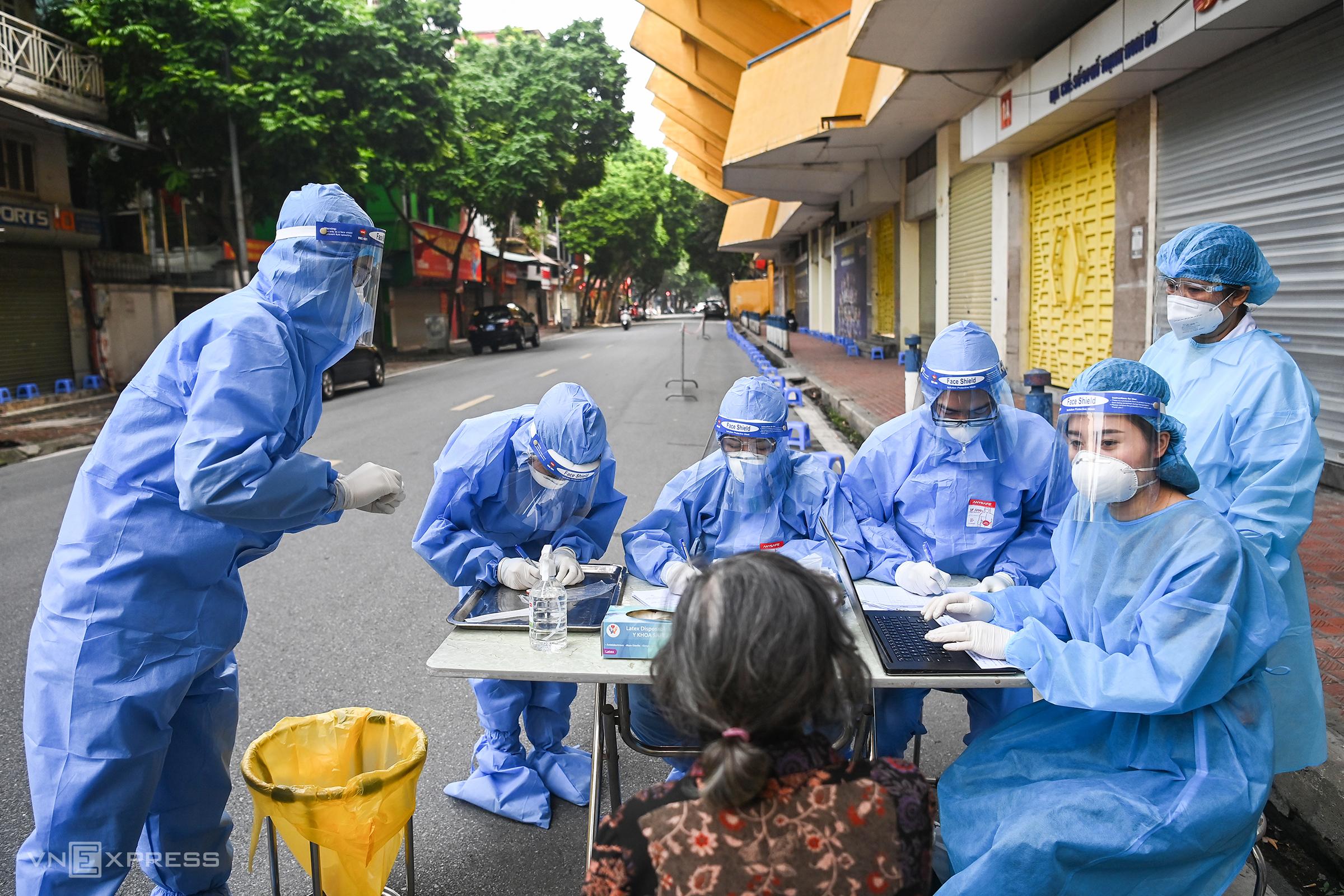 Nhân viên y tế lấy mẫu xét nghiệm cho người dân Hà Nội trước khi tiêm vaccine, ngày 10/9. Ảnh: Giang Huy