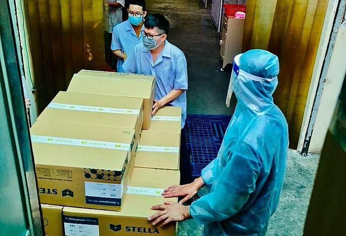 Các đơn vị quận huyện nhận thuốc kháng virus Molnupiravir tại kho, tối 26/9. Ảnh: N.L