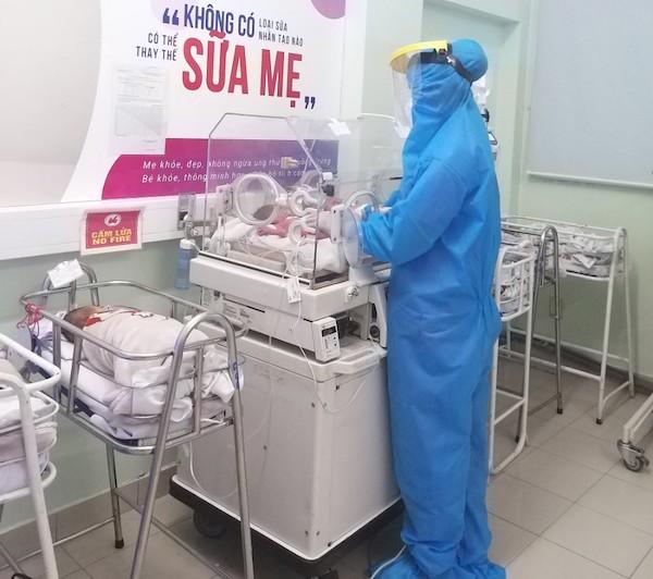 Điều dưỡng Lê Trần Thanh Mai trong trang phục bảo hộ đang chăm sóc cho một bé thiếu tháng trong lồng ấp. Ảnh. Nhân vật cung cấp