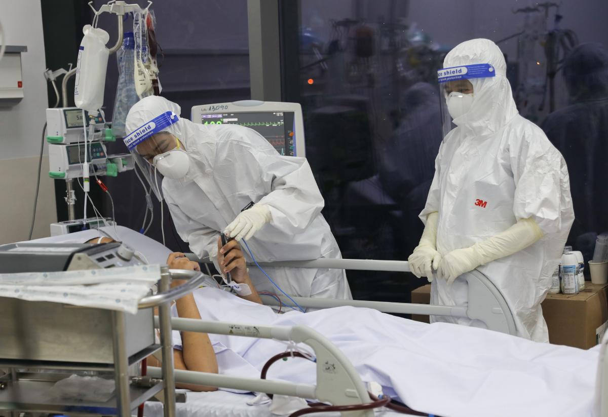 Nhân viên y tế hỏi số điện thoại người nhà từ một F0 tại Bệnh viện hồi sức Covid-19, khi bệnh nhân còn tỉnh táo. Ảnh: Quỳnh Trần