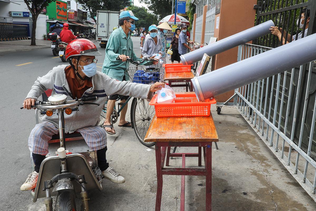 Người dân lấy cơm miễn phí qua ống nhựa để giãn cách phòng Covid-19 tại nhà thờ Tân Sa Châu, quận Tân Bình, ngày 26/6. Ảnh:Quỳnh Trần