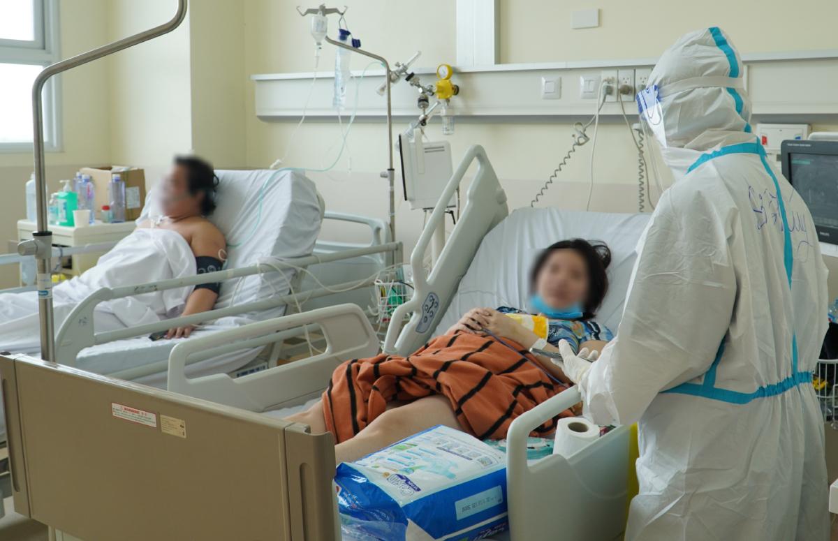 Nữ tu, Tiến sĩ tâm lý Trì Thị Minh Thúy trò chuyện với một bệnh nhân tại Bệnh viện Hồi sức Covid-19. Ảnh: Bệnh viện cung cấp