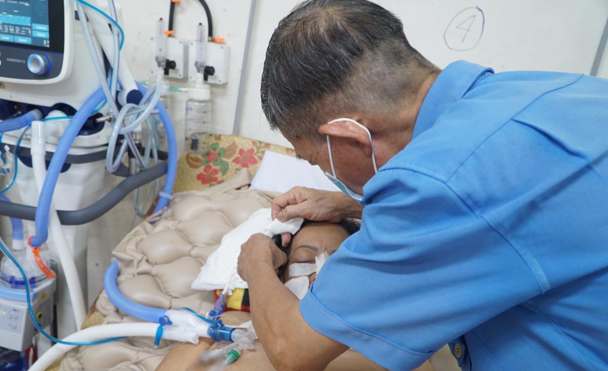 Ông Chính đang dùng khăn chấm nhẹ những giọt mồ hôi trên trán vợ, ngày 21/9. Ảnh: Thư Anh