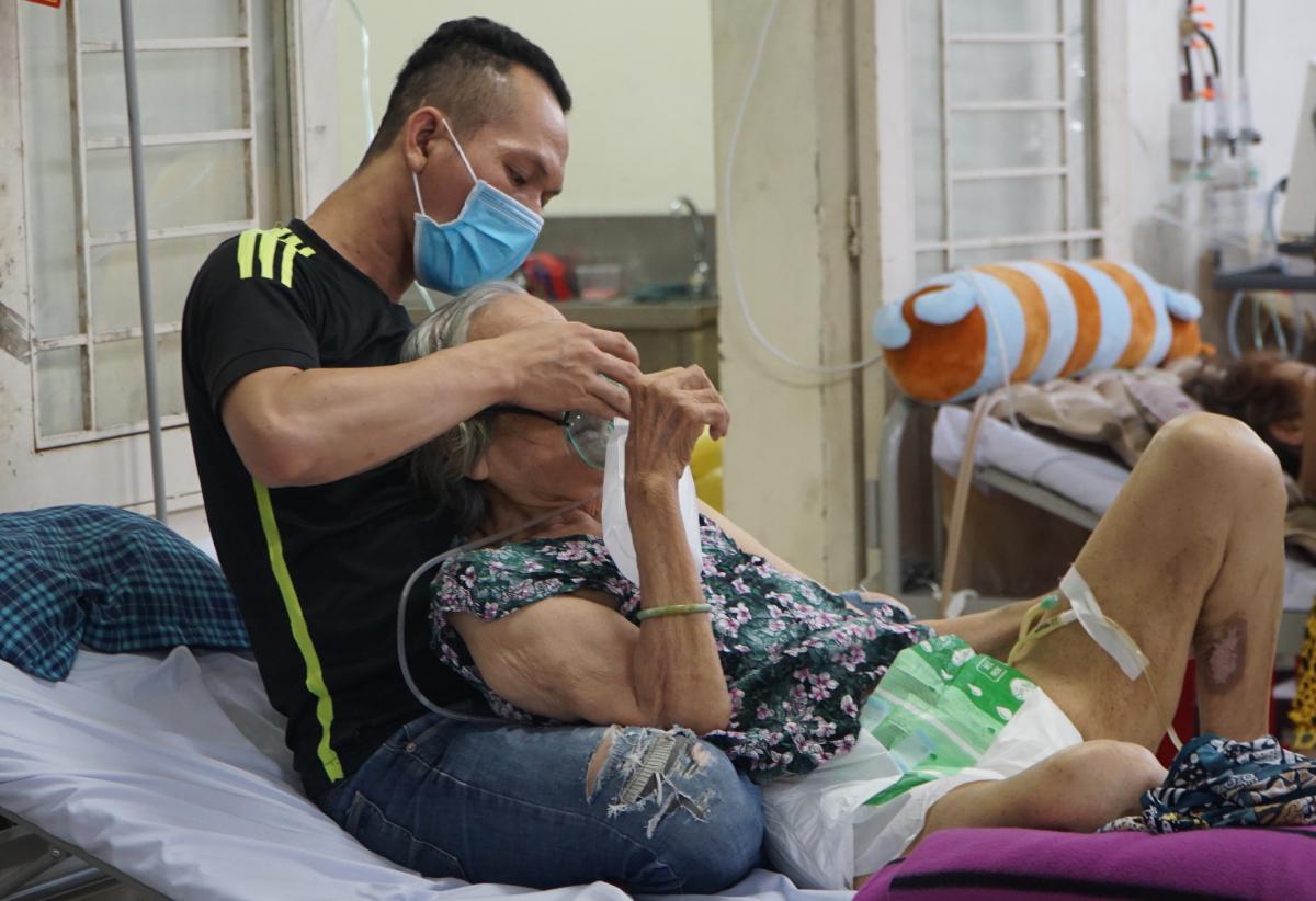 Anh Quang chỉnh lại mặt nạ oxy cho bà ngoại, sau khi nâng bà cụ ngồi dựa vào ngực anh cho dễ thở. Ảnh: Thư Anh