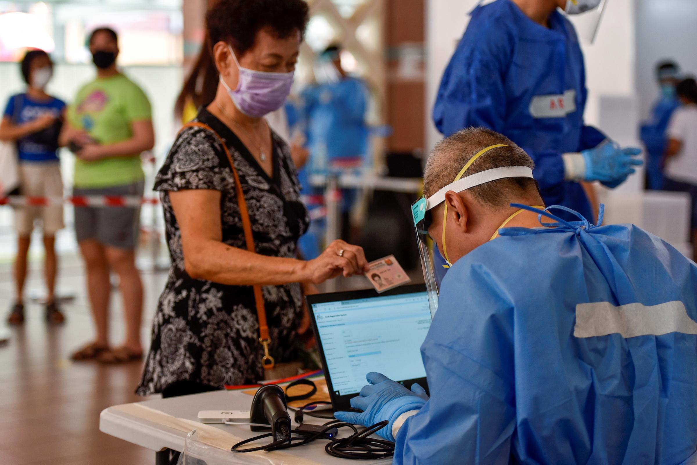 Nhân viên y tế Singapore kiểm tra thông tin của một người tới xét nghiệm nCoV ngày 16/6. Ảnh: Reuters
