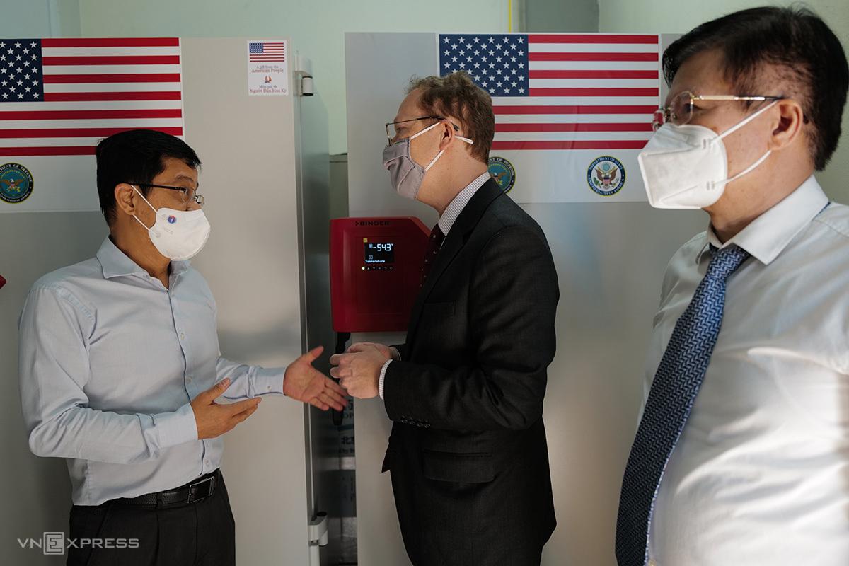 Đại biện lâm thời Mỹ tại Việt Nam Christopher Kline trao đổi với Thứ trưởng Y tế Trương Quốc Cường bên hai chiếc tủ lạnh âm sâu trong số tủ lạnh bàn giao chiều 12/10. Ảnh: Ngọc Thành
